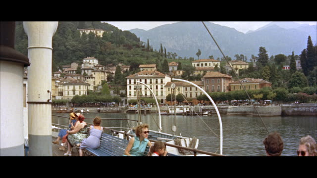 ms people sitting in boat / lake como, italy. - anno 1956 video stock e b–roll