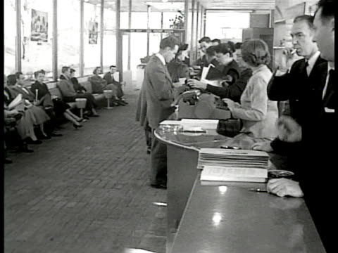 people sitting in chairs along glass wall pan to sales counter w/ salespeople helping customers fill out paperwork - levittown pennsylvania stock videos and b-roll footage