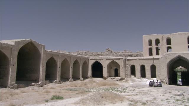 ws pan people sitting in courtyard of caravanserai, iran - inn stock videos & royalty-free footage
