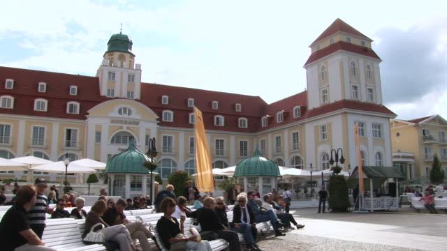 ms people sitting in front of kushaus casino on rã¼gen island   / binz, mecklenburg-western pomerania, germany - kasino stock-videos und b-roll-filmmaterial