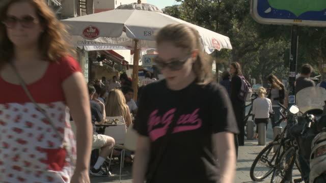 ms pan people sitting in sidewalk cafe, pedestrians walking past / tel aviv, israel - tel aviv stock videos & royalty-free footage