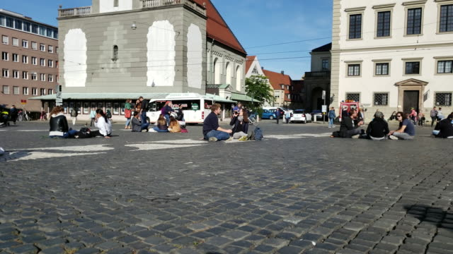 vidéos et rushes de people sitting in town square enjoying summer in augsburg germany - rathaus