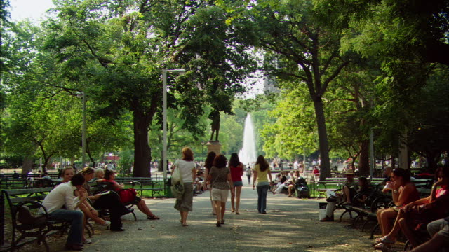 vídeos y material grabado en eventos de stock de ws people sitting near and walking toward fountain in washington square park / manhattan, new york, usa - moving past