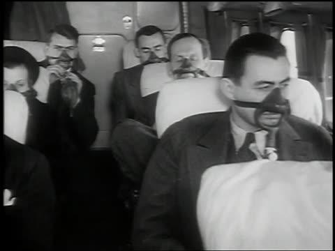 b/w 1939 ms pan people sitting on airplane wearing oxygen masks - vehicle seat stock videos & royalty-free footage