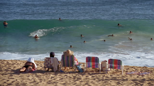 people sitting on beach chairs watching bodyboarders ride shorebreak at sandy beach / south shore, oahu, hawaii - oahu bildbanksvideor och videomaterial från bakom kulisserna