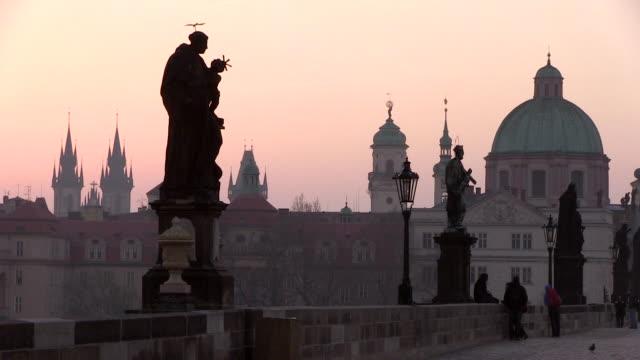 MS People sitting on charles bridge at morning and pink glow sky background / Prague, Hlavni mesto Praha, Czech Republic