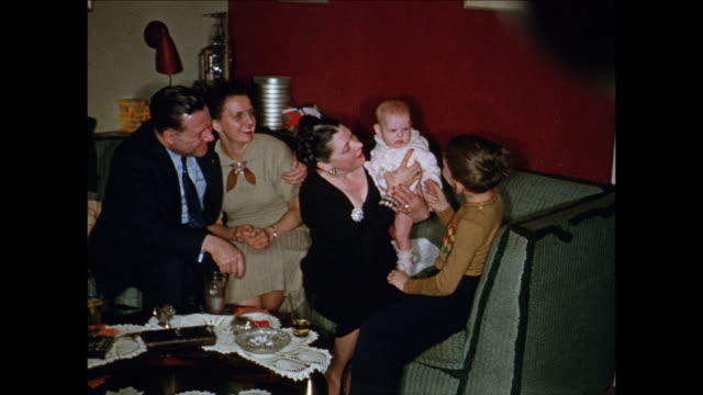 vidéos et rushes de 1955 montage people sitting on couch cuddling baby girl (12 months) / toronto, canada - 12 17 mois