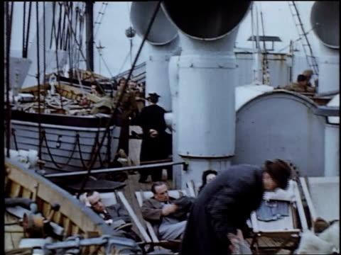 people sitting on deck chairs beneath ventilation shaft aboard ship / united kingdom - einige gegenstände mittelgroße ansammlung stock-videos und b-roll-filmmaterial