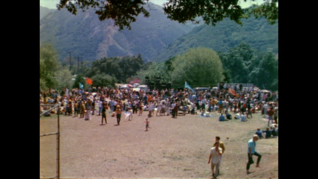 vídeos de stock e filmes b-roll de / people sitting on hillside during lovein at tapia park / view of people dancing below near stage hippies on the hillside at tapia park lovein on... - love in