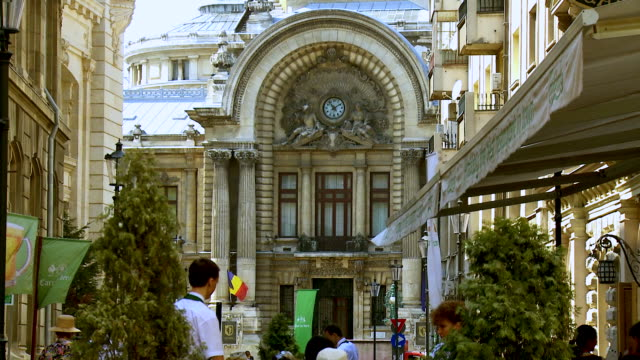 ms zo people sitting on outdoor dining area in front of historic national savings bank building / bucharest, romania - romania stock videos & royalty-free footage