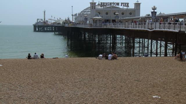 ws tu people sitting on pebble beach facing brighton pier / brighton, united kingdom - ブライトン パレスピア点の映像素材/bロール