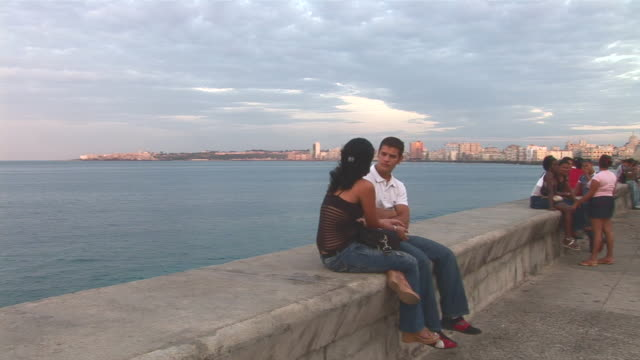 stockvideo's en b-roll-footage met ws pan people sitting on wall of malecon boulevard at sunset / havana city, havana, cuba - boulevard