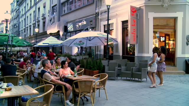 MS PAN People sitting outdoor dining and beside pedestrians walking  / Bucharest, Romania