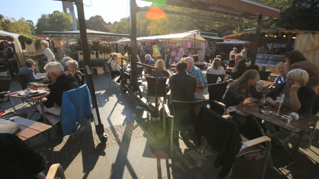People sitting outside café on sunny day in Berlin