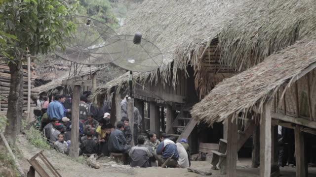 ws people sitting outside huts / xam neua, laos - tetto di paglia video stock e b–roll