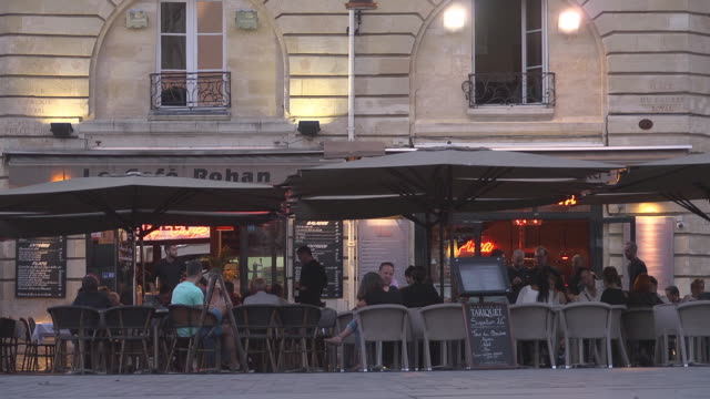 people sitting outside of a restaurant - evening