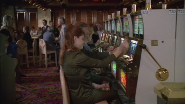 MS PAN People sitting, playing on slot machines in casino, two women throwing won chips in the air / Las Vegas, Nevada, USA