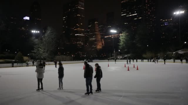 people skate at the wollman ice skating rink in central park at night on february 2 a wide shot of people ice skating at the wollman rink, a medium... - ice skating stock videos & royalty-free footage