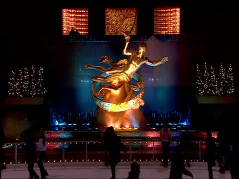 people skate on ice-rink beneath gold statue illuminated at night at rockefeller center manhattan - rockefeller centre stock videos & royalty-free footage