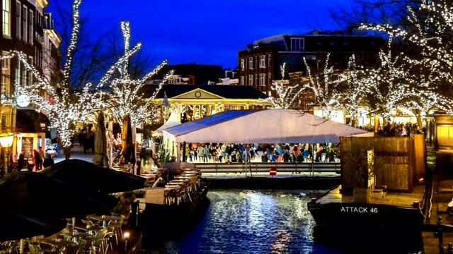 people skating on a floating skating-rink on christmas market in the old town of leiden at night. this market is unique in the world because it is a market floating on the water, canal - dutch culture stock videos & royalty-free footage