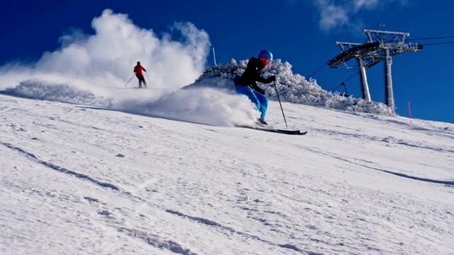 SLO MO People skiing down ski slope