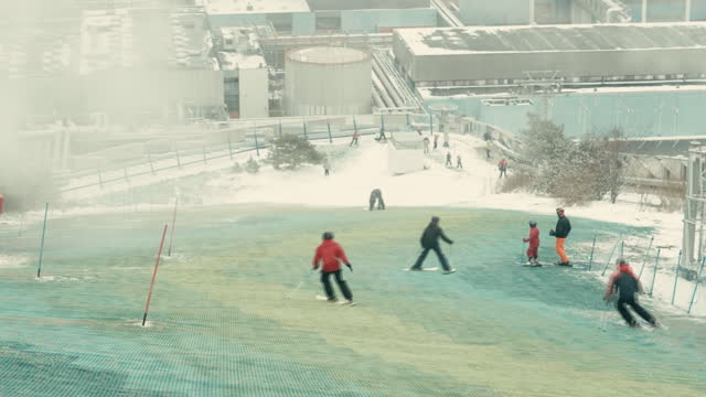 people skiing on artificial ski slope at amager bakke, also known as copenhill, a waste-to-energy plant in copenhagen, hovedstaden, denmark, on... - creativity stock videos & royalty-free footage