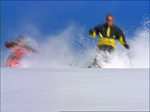 2 people skiing quickly towards camera / one wipes out - real time stock videos & royalty-free footage