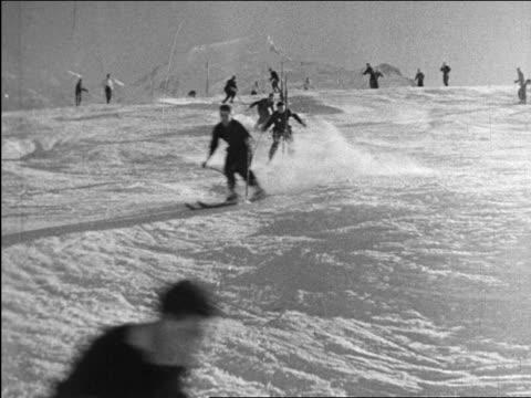 b/w 1940 people slalom skiing towards camera / industrial - slalom skiing stock videos & royalty-free footage