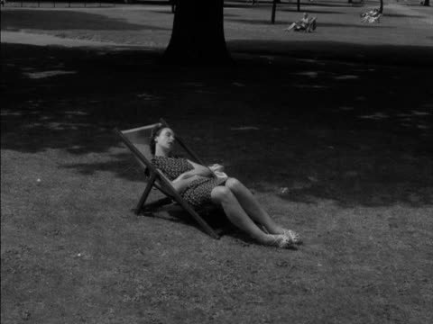vidéos et rushes de people sleep and relax in deckchairs in regents park. 1955. - napping
