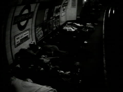people sleeping on subway platform people reclined on floor woman reading. man sleeping next to man reading. wwii london blitz bomb shelter air raid... - bomb shelter stock videos & royalty-free footage