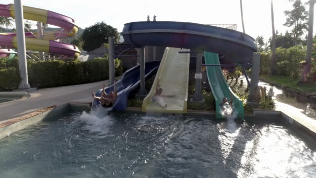 people sliding down  the water rides at a water park - fairground ride stock videos & royalty-free footage