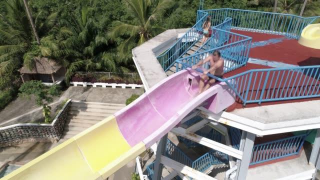 vídeos de stock, filmes e b-roll de pessoas descendo a água desliza num parque de diversões - tobogã d'água