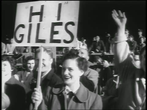 b/w 1954 people smiling waving to returning soldiers / woman holds hi giles sign - 1954 stock videos and b-roll footage