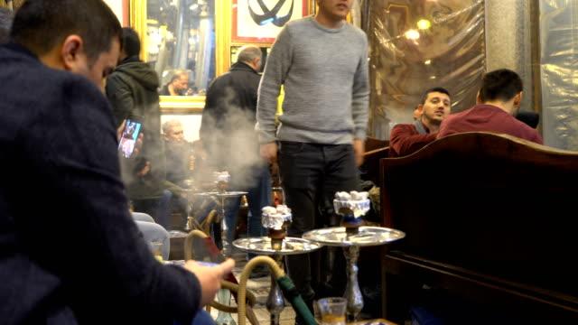 people smoking shisha at nargile cafe, shisha place around grand bazaar - トルコ点の映像素材/bロール
