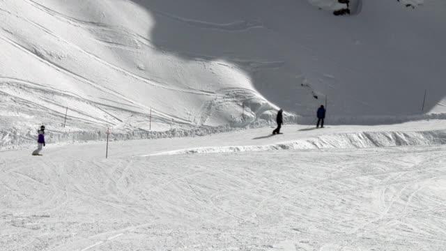 stockvideo's en b-roll-footage met people snowboarding and skiing at ski resort - skigebied