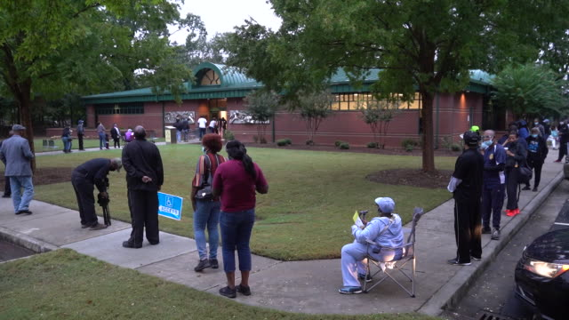 people social distancing while waiting in line to vote on the first day of early voting in atlanta, georgia, u.s. on monday, october 12, 2020. - ジョージア州点の映像素材/bロール