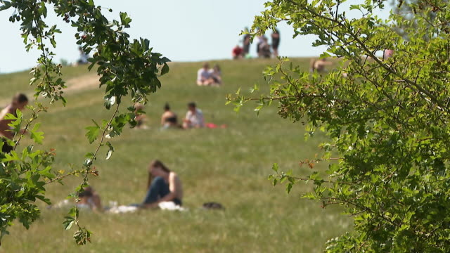 people socialising outdoors in parks as some coronavirus lockdown restrictions are eased london - sunbathing stock videos & royalty-free footage