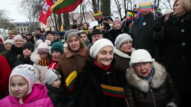 People some bearing Lithuanian flags attend a state ceremony outside the Presidential Palace to mark the 100th anniversary of the restoration of...
