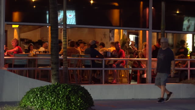 people some wearing face coverings dine on an outdoor patio at bo's beach restaurant on fort lauderdale beach boulevard on october 9 fort lauderdale... - scott mcpartland stock videos & royalty-free footage