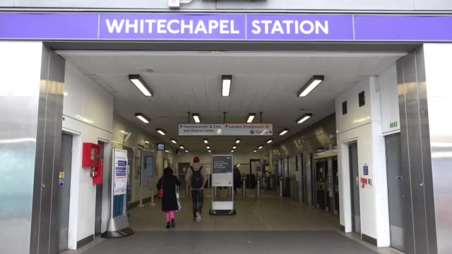 people some wearing protective face masks enter and exit whitechapel underground station as the call to prayer can be heard from the nearby east... - mosque stock videos & royalty-free footage