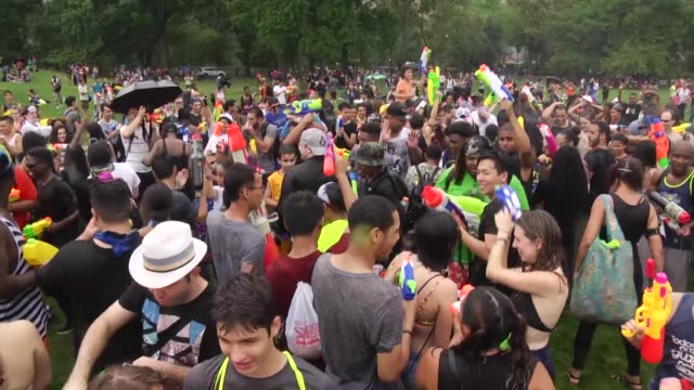 people spray water with water guns during a water-fight at sheep meadow event in new york city on july 30, 2016. - water fight stock videos & royalty-free footage
