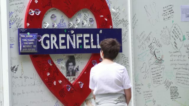 people stand and pay their respects in front of a wall where messages of support have been written surrounding grenfell tower in west london on june... - fire natural phenomenon stock videos & royalty-free footage