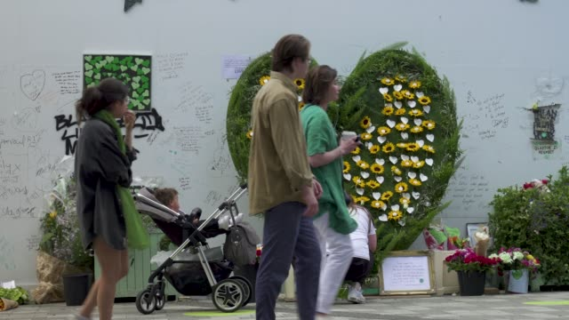 people stand and pay their respects in front of a wall where messages of support have been written, surrounding grenfell tower in west london on june... - surrounding wall点の映像素材/bロール
