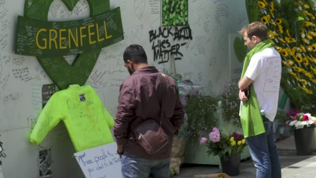 people stand and pay their respects in front of a wall where messages of support have been written, surrounding grenfell tower in west london on june... - surrounding wall stock-videos und b-roll-filmmaterial