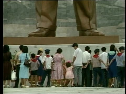 People stand at foot of giant statue of Kim Il Sung North Korea Feb 88