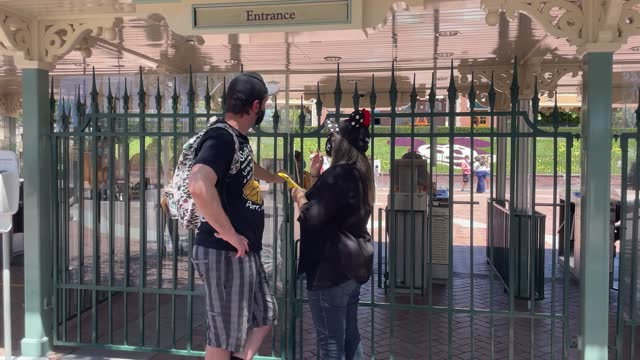people stand at the gated entrance as disneyland and disney's california adventure reopens with social distancing and a reduced crowd at the... - anaheim california stock videos & royalty-free footage
