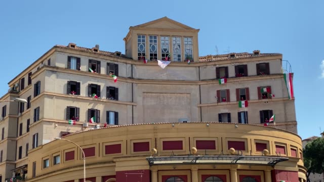 """stockvideo's en b-roll-footage met people stand at their windows and balconies while to take part in a 'liberation day' flashmob and sing the italian partizan song """"bella ciao"""" at... - balkon"""