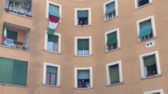 """people stand at their windows and balconies while to take part in a 'liberation day' flashmob and sing the italian partizan song """"bella ciao"""" at... - singing stock videos & royalty-free footage"""