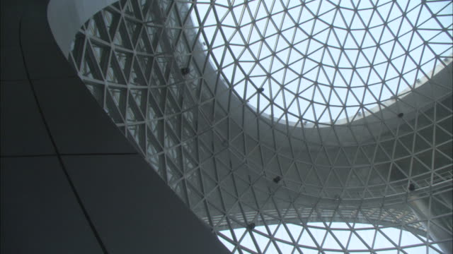 People stand beneath a large grated dome.