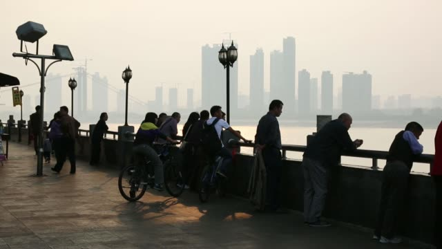 People stand beside the Chang Jiang river with the television tower center in the background in Wuhan China on Sunday Oct 20 People stand looking at...